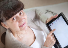 Pension age good looking woman looking internet in tablet device. Stock Photo