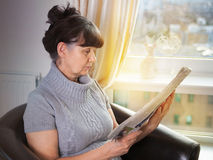 Pension age good looking woman reading the news paper Royalty Free Stock Image