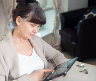 Pension age good looking woman searching in internet Royalty Free Stock Photos