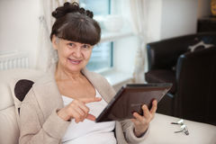Pension age good looking woman searching in internet Royalty Free Stock Image