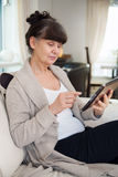 Pension age good looking woman with tablet Royalty Free Stock Image