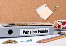 Pension Funds. Folder on office desk. Money, Coffee Mug and colored pencilsr Royalty Free Stock Images