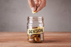 Pension. Glass jar with coins and an inscription pension. Man holds coin in his hand.  stock photo