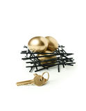 Pension Nest Egg. Concept image for pension planning Golden goose eggs in a stark wooden birds nest with gold keys against a white background. Copy space Royalty Free Stock Photos