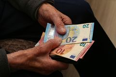 Pension. / Money in the hands of an old man stock images