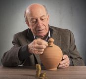 Pension and savings. Old man keeps pension in a piggybank Stock Photos