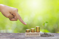 PENSION WORD WITH BUSINESSMAN HAND POINTING TO STACK OF GOLD COI Royalty Free Stock Photo