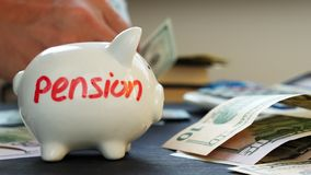 Pension written on a piggy bank and hands counting money. Retirement planning. stock video footage