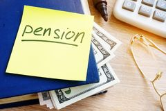 Pension written on a stick and money. Retirement savings. Stock Photography
