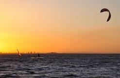 Pensionante del cervo volante e surfista del vento al tramonto Immagini Stock