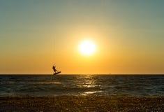 Pensionante dell'aquilone che esegue un salto al tramonto Fotografia Stock