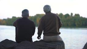 Pensionati anziani che gettano le pietre in acqua, sedentesi sulla sponda del fiume, resto di fine settimana video d archivio