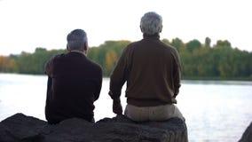 Pensionati anziani che godono della foresta e dell'acqua che si siedono sulla sponda del fiume, resto di fine settimana fotografia stock libera da diritti