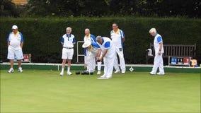 Pensionati del oap dei membri senior che giocano gli sport attivi di campo da bocce delle ciotole all'aperto stock footage