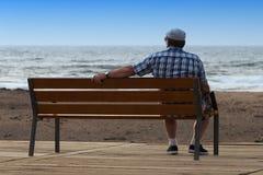 Pensionato che si siede su un banco Immagini Stock