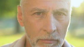 Pensionato dai capelli grigio che esamina macchina fotografica, sicurezza sociale e pensionamento archivi video