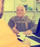 Pensionato e l'agente firma il contratto assicurativo Fotografie Stock Libere da Diritti
