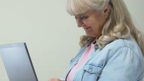Pensionato femminile che scrive sul computer portatile e sulla macchina fotografica sorridente, attività bancarie online, Interne archivi video