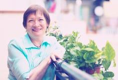 Pensionato femminile sorridente che riposa al balcone Immagini Stock Libere da Diritti