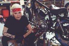 Pensionato pensieroso che si siede accanto al motociclo fotografia stock libera da diritti