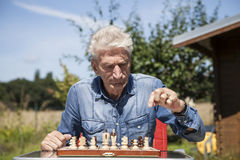 Pensioner with chessboard Royalty Free Stock Photos