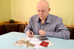 The pensioner considers cash expenditures on utility payments Royalty Free Stock Images