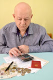The pensioner counts on the calculator cash expenditures on utility payments Royalty Free Stock Photo