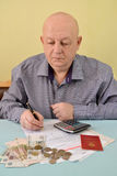 The pensioner counts cash expenditures on utility payments Royalty Free Stock Photography