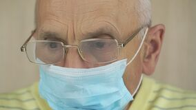 Pensioner in disposable mask and glasses in isolation