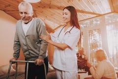 Pensioner on Go-Carts. Caregiver. Adult Caucasian. Asian Nurse. Helps. Adult Walker. Nursing Home. Hard Go Himself. Doctor Supports Man. Nurse Hold. Old Bones stock image