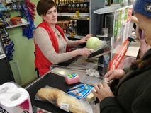 Pensioner grandmother takes out money from the wallet and pays the purchase at the supermarket at the checkout. royalty free stock photography