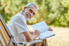 Pensioner holding a book and smiling Royalty Free Stock Images