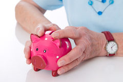 Pensioner holding her piggy bank Stock Image