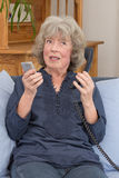 Pensioner with landline and smartphone Royalty Free Stock Photography