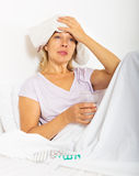 Pensioner laying in bed with towel on forehead Royalty Free Stock Images