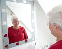 Pensioner looking in the mirror Stock Photography