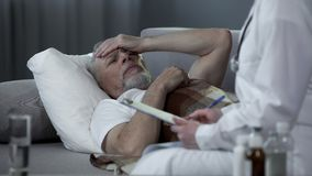 Pensioner lying in bed and talking with therapist about disease, health care. Stock footage Stock Photography