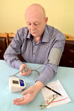 The pensioner measures pressure by an electronic tonometer semiautomatic device.  royalty free stock photos