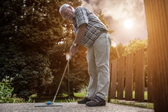 A pensioner at a minigolf court. He starts to prepare to push th Stock Photo