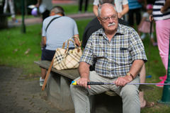 Pensioner at a minigolf court is waiting on a park bench and wat Royalty Free Stock Image