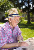 Pensioner with newspaper Royalty Free Stock Image