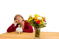 Pensioner with a piggy bank. Pensioner sitting with a piggy bank on a table Stock Image
