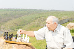 Pensioner playing chess outdoors Royalty Free Stock Photo