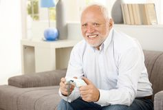 Pensioner playing computer game. Modern pensioner playing computer game on sofa, smiling Royalty Free Stock Photo