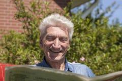 Pensioner reading amused newspaper Stock Photos