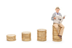 Pensioner reading the news on a pile of coins Royalty Free Stock Photo