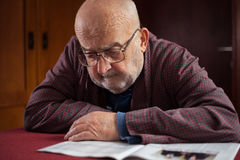 Pensioner reading newspaper Royalty Free Stock Photos