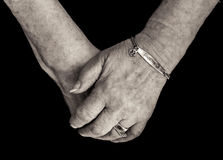 Pensioner`s hands with medical alert bracelet for diabetes. Mono. Elderly woman`s hands wearing a medical alert bracelet for diabetes. Close up on a black royalty free stock photography