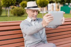 A pensioner sits on a bench in a beautiful square. He has a gray tablet in hands. He communicates by video with someone Stock Photography