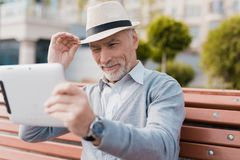 A pensioner sits on a bench in a beautiful square. He has a gray tablet in hands. He communicates by video with someone Stock Images